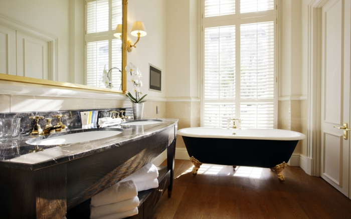 decoración moderna, baños pequeños, lavabo con encimera de mármol, bañera con partas de garra doradas, espejo grande, ventanal con persianas, suelo laminado