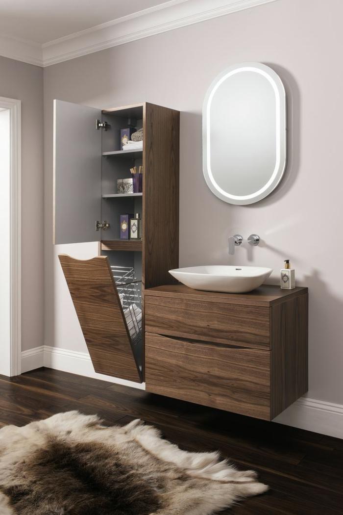 baños pequeños, armarios de madera funcionales, lavabo pequeño, espejo ovalado, suelo laminado, alfombra piel de vaca