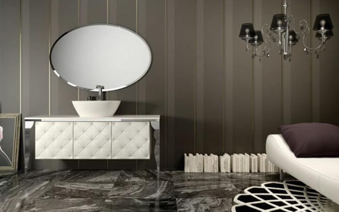baño lujoso, espejo oval, lavabo con mueble tapizado en capitoné, piel banca, banco y lámpara de araña, suelo con baldosas