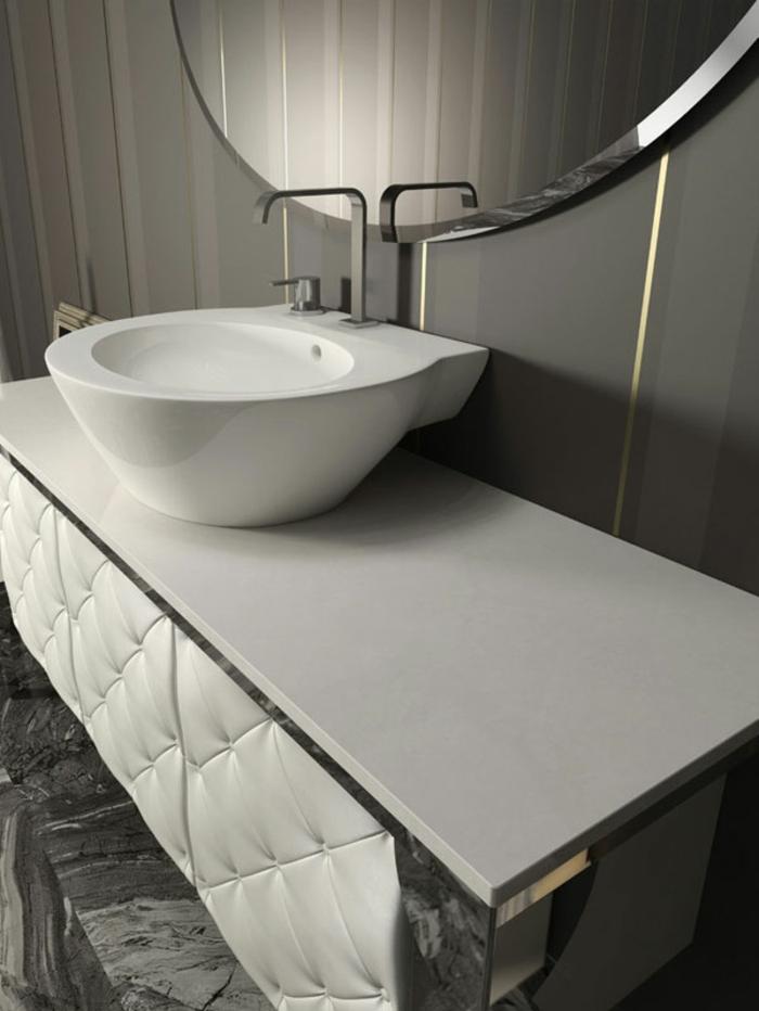 mueble lavabo moderno tapizado en capitoné blanco, muebles de baño modernos detalle, lavabo pequeño, espejo redondo