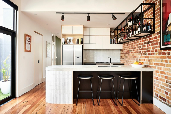 idea moderna para diseñar cocinas industriales, cocina en l con grande barra en blanco, paredes de ladrillos y suelo de parquet