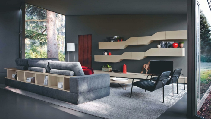 estilo moderno, paredes de vidrio, colores para pintar un salon, pared en gris oscuro, estanterías modernas, sofá gris con espacio de almacenamiento, sillas negras, alfombra