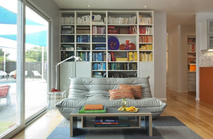 librería de plástico, salón moderno con terraza, mesita rectangular, sofá gris con cojines color naranja, tapete azul
