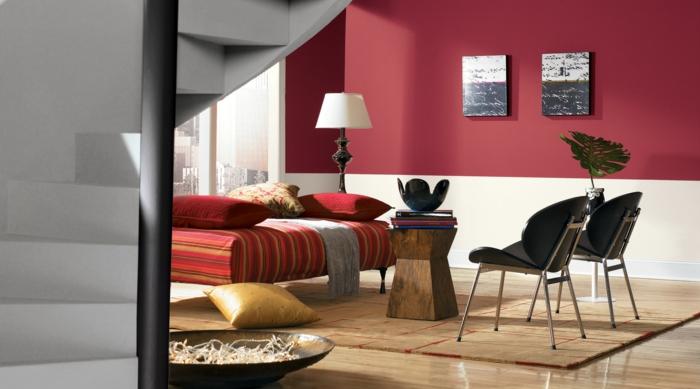 combinacion de colores, sala de estar con paredes en rojo y beige, ventanal sin cortinas, banco rojo con cojines, sillas negras, sulo laminado con tapete
