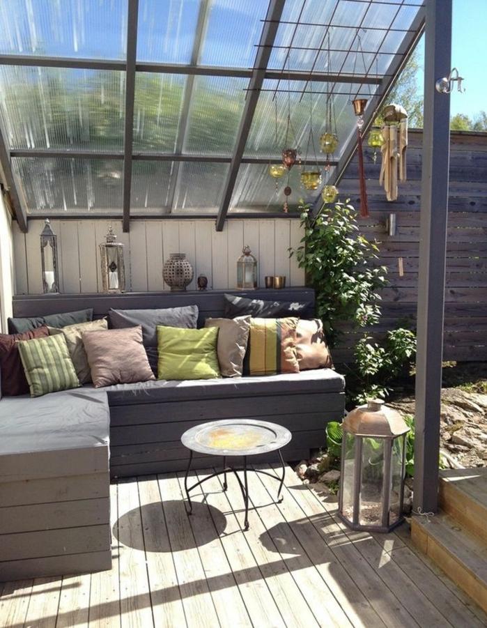 decoración de terrazas modernas en colores terrosos, cojines pequeños decorativos, mesa baja de hierro forjado, techo nivelado