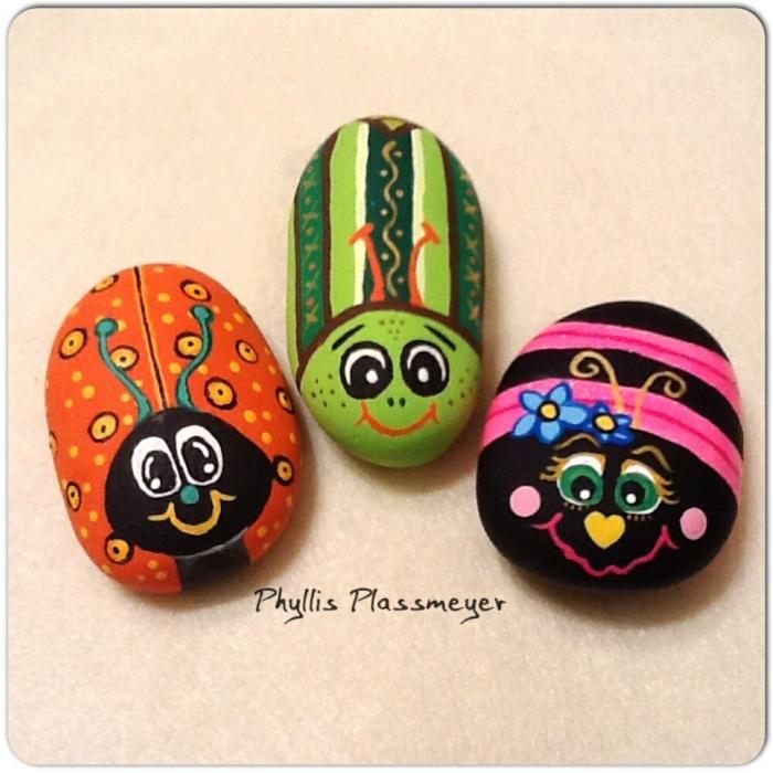 pintar piedras, manualidades infantiles, piedras pintadas como mariquitas y abejas en rosado, color naranja y verde, decoración casera
