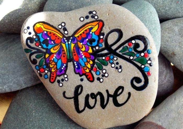 pintar piedras, piedra natural plana grande, pintura acrilica, mariposa de colores, palabra love and negro cursiva