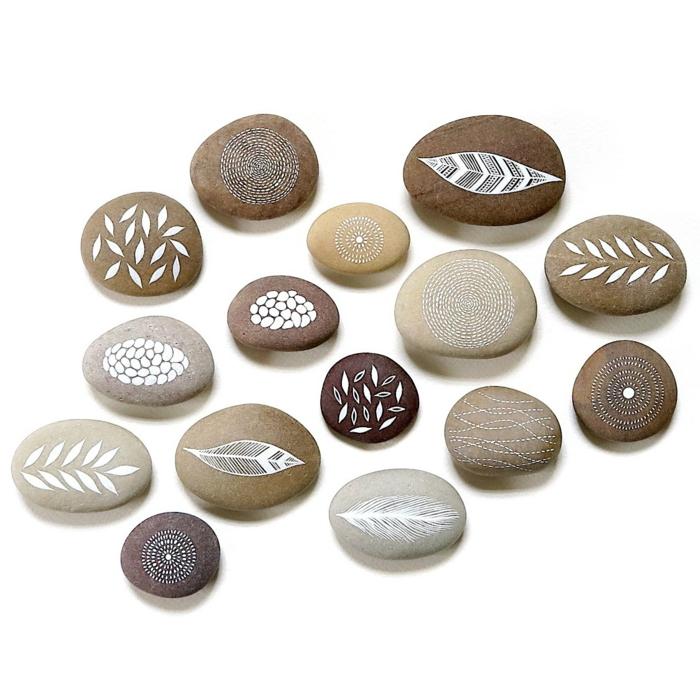 pintar piedras, piedras fluviales planas decoradas con hojas y motivos florales con pintura blanca, decoración para jardines