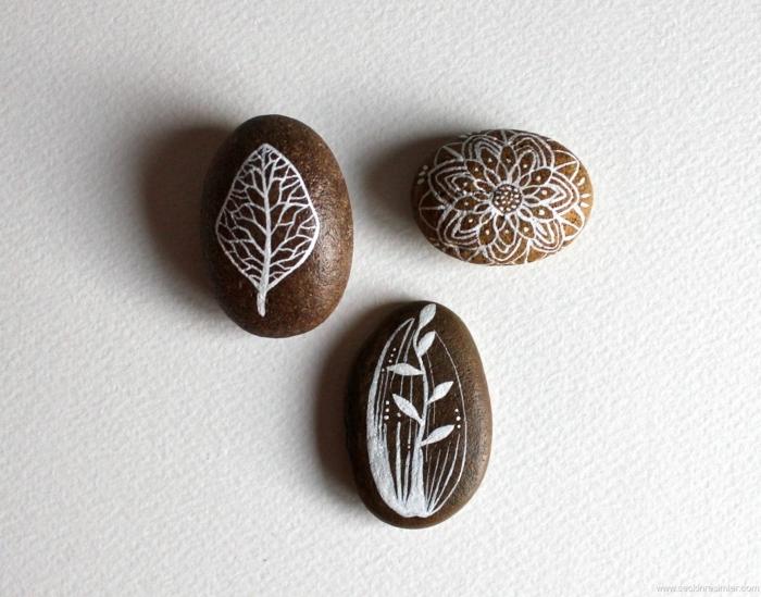 ideas para dibujar, piedras decorativas marrones pintadas con blanco acrilico, motivos naturales, decoración jardín