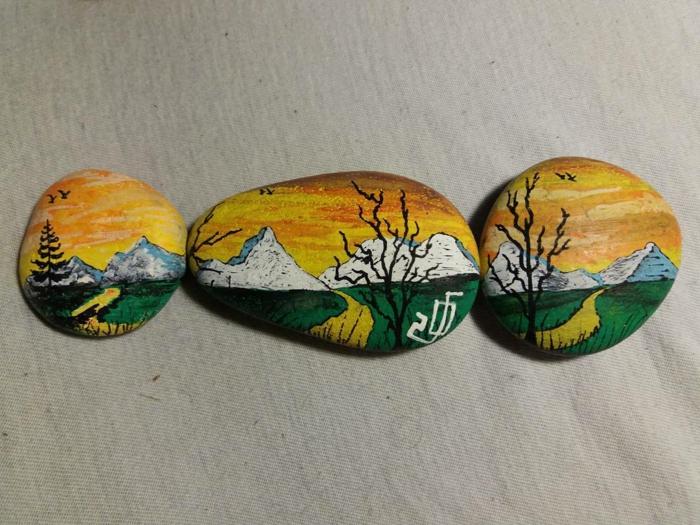 manualidades con piedras, composición con piedras pintadas, paisaje natural con montañas nevadas y horizonte amarillo