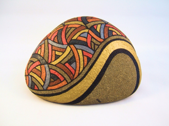 pintar piedras, piedra natural, pintura acrilica con brillo, lineas de color entrelazadas con negro y dorado, manualidades faciles