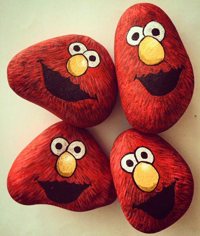 piedras para jardin, manualidades para niños, cuatro piedras pintadas con acrilico, la cara de Elmo sonriente