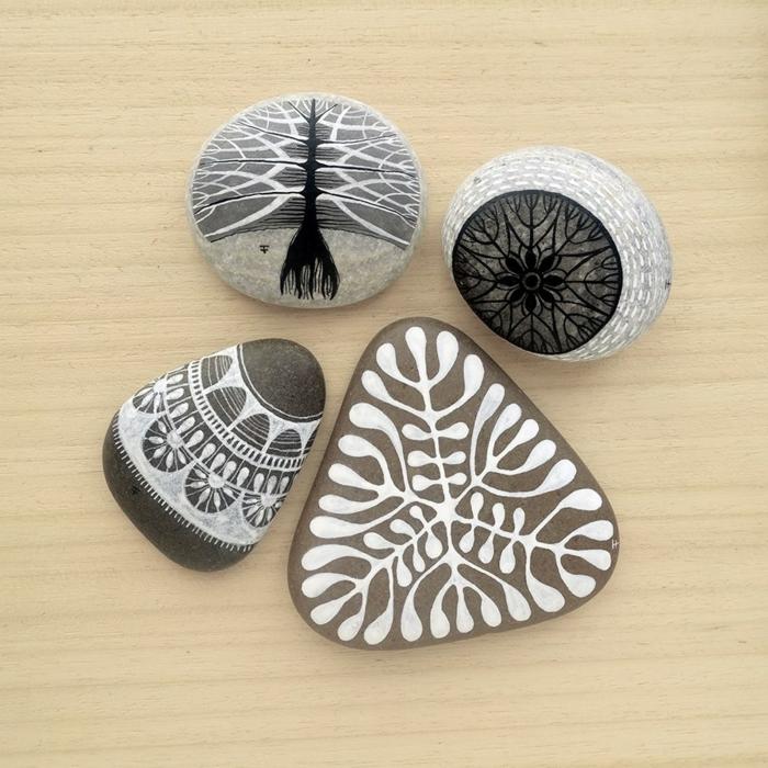 manualidades con piedras, piedras grises pintadas con pntura acrilica en blanco y negro, dibujos abstractos, decoración casera