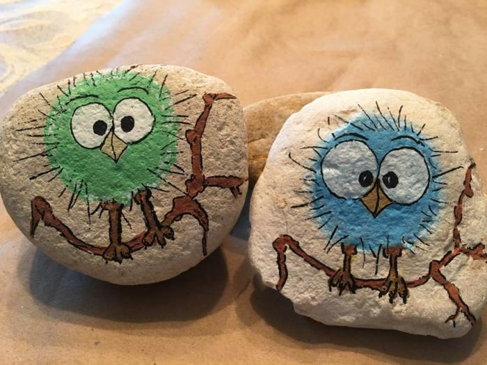 pintar piedras, piedras naturales escarbosos pintadas con pajaritos sobre ramos en verde y azul, manualidades para niños