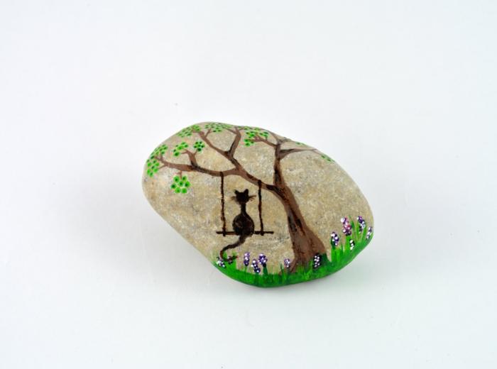 pintar paredes, manualidades para niños, piedra natural, dibujo de gato sobre columpio, flores y árbol