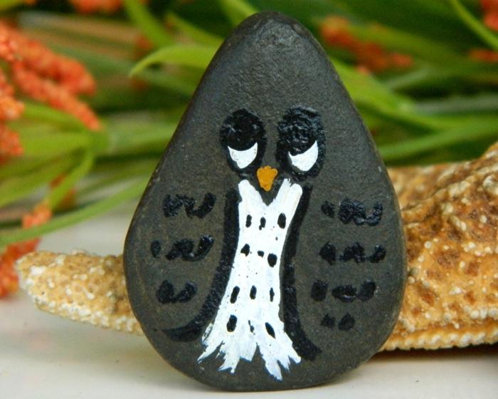 pintar piedras, piedra gris oscuro en forma de huevo pintada como un buho, pintura acrilica, imagen divertida, decoración casera