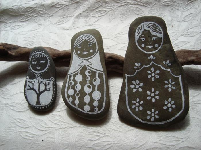 manualidades con piedras, piedras naturales en gris oscuro, pintadas con pintura acrilica, imagen de matryoshka rusa