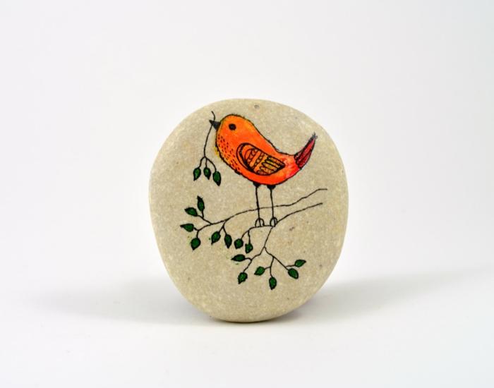 piedras pintadas a mano, manualidades faciles, piedra blanca con dibujo de pájaro con rama en el pico, verde, anaranjado