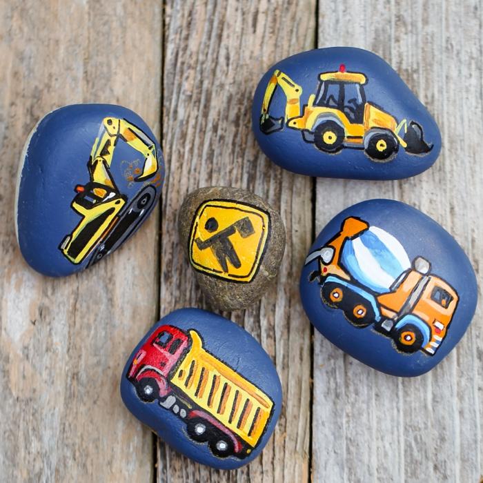 ideas para pintar, composición de piedras pintadas con fondo azul y máquinas de construcción, decoración para niños, manualidades