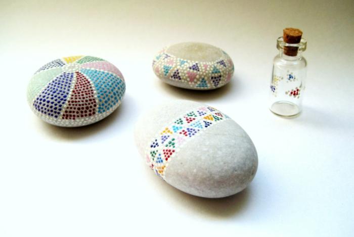 ideas para dibujar, piedras blancas decoradas con puntitos de color en triángulos, decoración para macetas