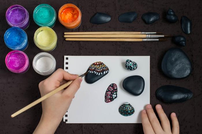 piedras para jardin, como pintar piedras con pintura acrilica multicolor, piedras planas negras decoradas con puntitos de color
