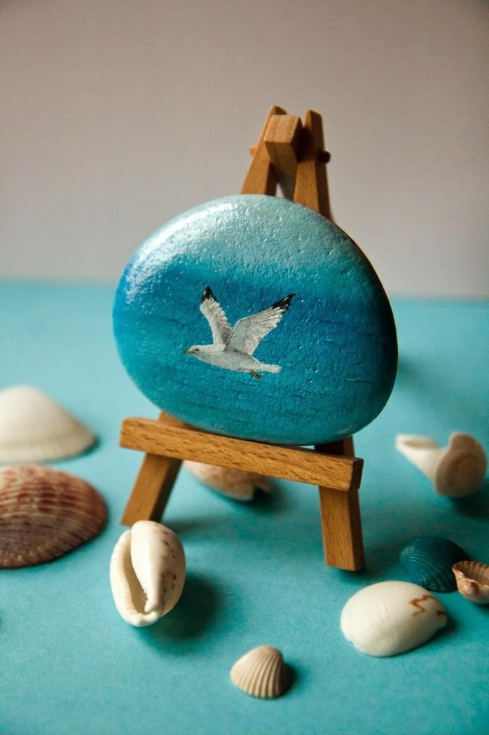 piedraspara jardin, arte en piedras, mini cuadro sobre piedra, gaviota volando en el cielo azul, mini caballete, conchas