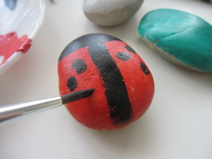 piedras para jardin, pintar piedras con pintura acrilica, piedra en rojo y negro como mariquita, foto del proceso