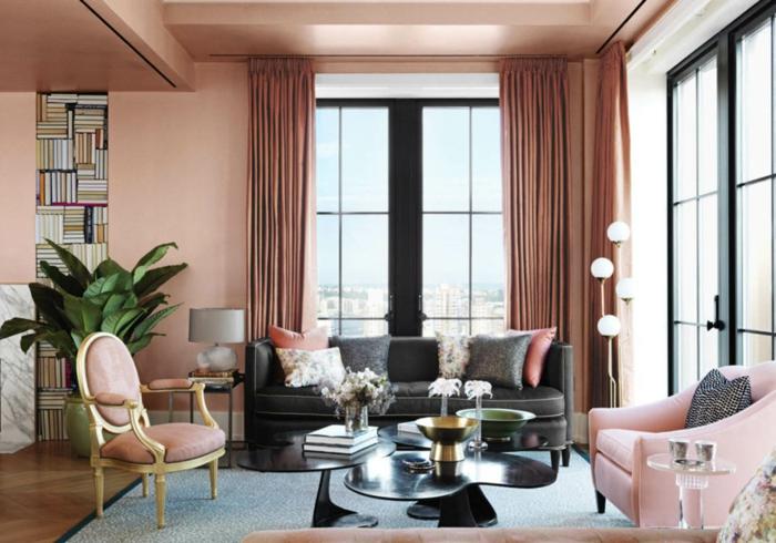 idea de decoración, colores para paredes, salón con paredes color melocoton, sofá negra con cojines, ventanales con cortinas masivas, planta verde