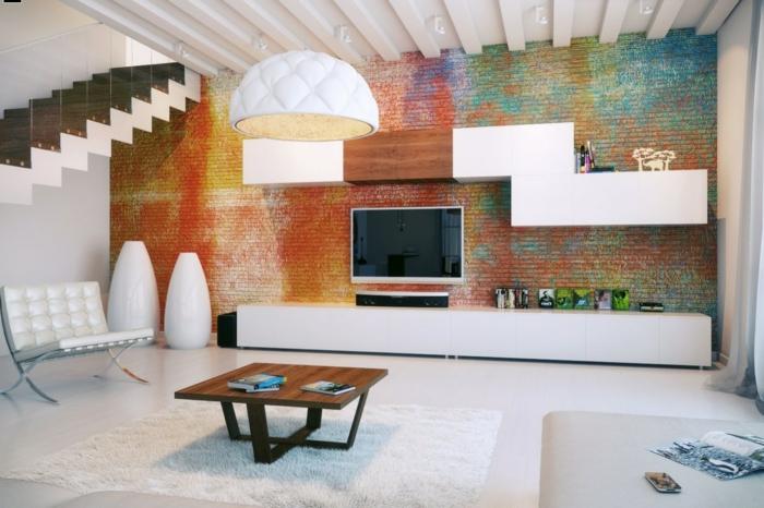 pintura para paredes, salón con techo alto y pared de ladrillo pintada multicolor efecto esponja, televisor, estanterías modernas, mesa de madera, lampara colgande blanca