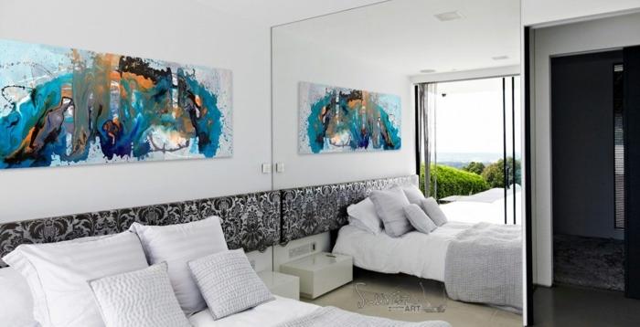 decorar el dormitorio con grandes cuadros, espejo grande, cama doble con cobijas en blanco, pintura impresionista