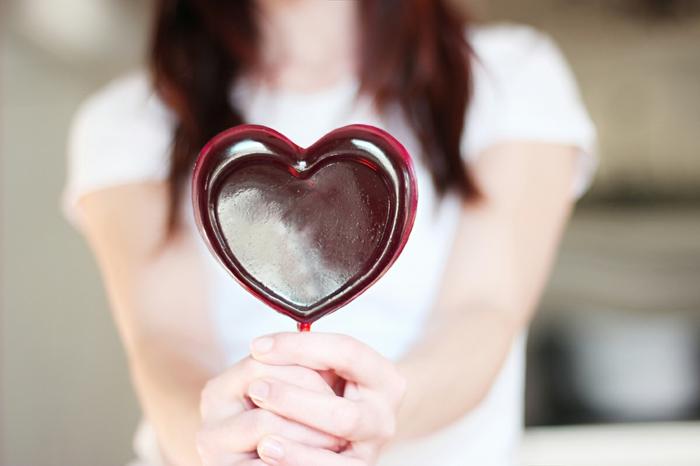 regalos originales para novios, mujer con piruleta roja en forma de corazon, idea de manualidad para san valentín, chupachups sabor vino tinto