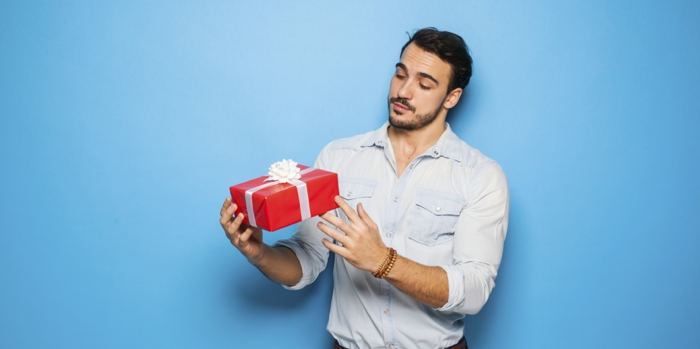como sorprender a tu novio, foto de hombre con barba en camisa colgando regalo empaquetado en rojo con lazo blanco