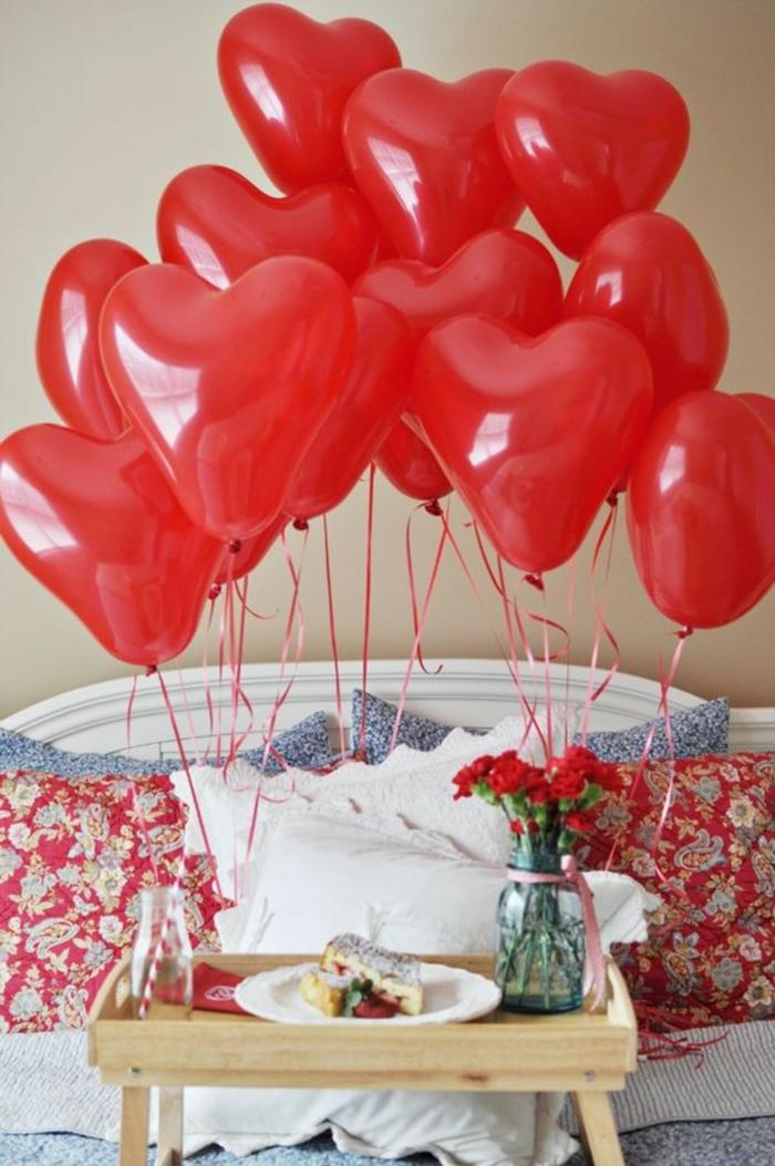 desayuno sorpresa con muchos globos rojos en forma de corazones, tablero de madera con piernas
