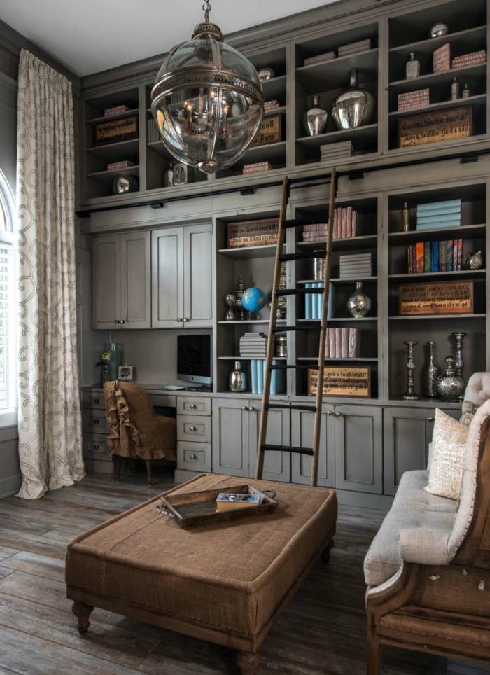 habitación despacho, librerias, armario con estantes y escritorio de madera gris, escalera de mano, sofá y mesa tapizados, suelo con tarima, lámpara colgante