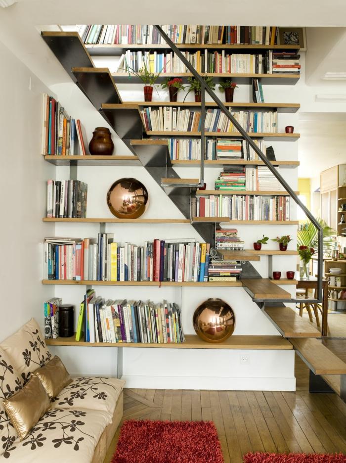 escalera de metal y madera, rincón de lectrua, baldas de madera, sofá pequeño en beige y forado, tapete rojo, librería con jarrones decorativos