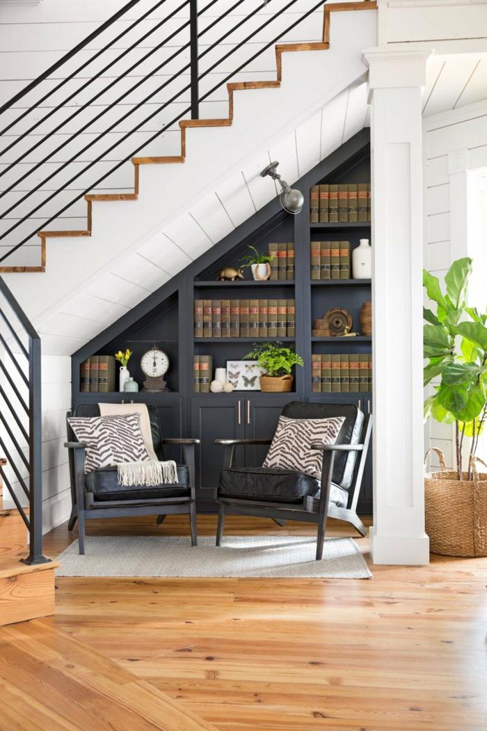 decoración moderna, casa con escalera, sillones de piel con cojines tipo zebra, librería de madera azul navy, suelo con parquet, planta verde