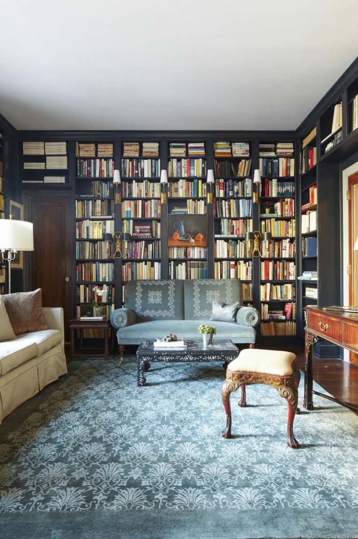 estanterias para libros, idea de decoración clásica, librría de madera gris de suelo a techo, tapete en azul grisáceo, taburete, escritorio vintage