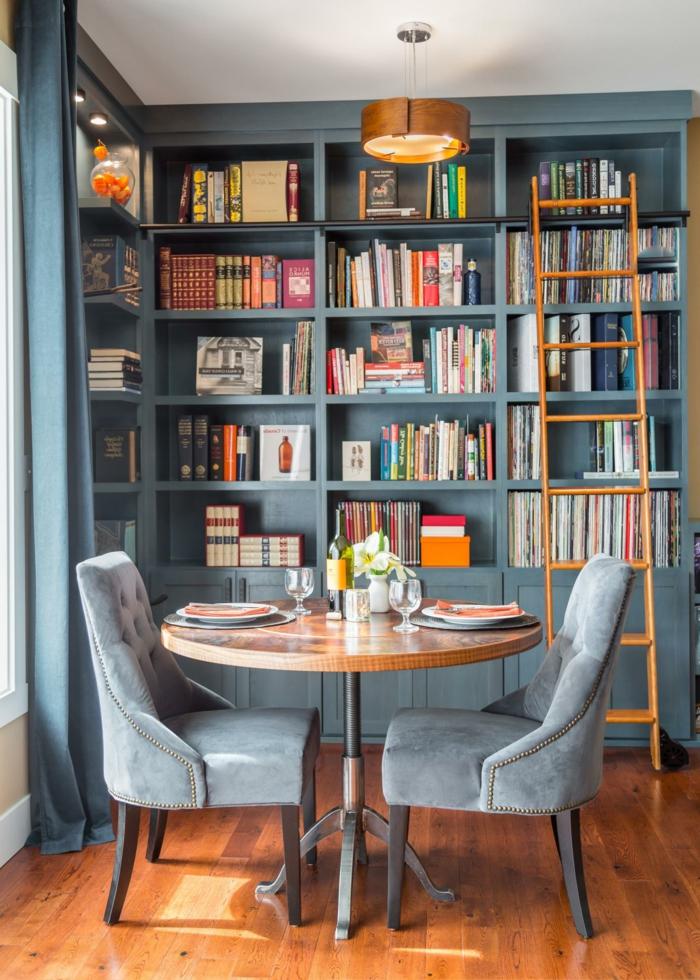 comedor para dos personas, estanterias para libros, decoración en azul grisáceo, mesa redonda, librería con escalera de mano madera