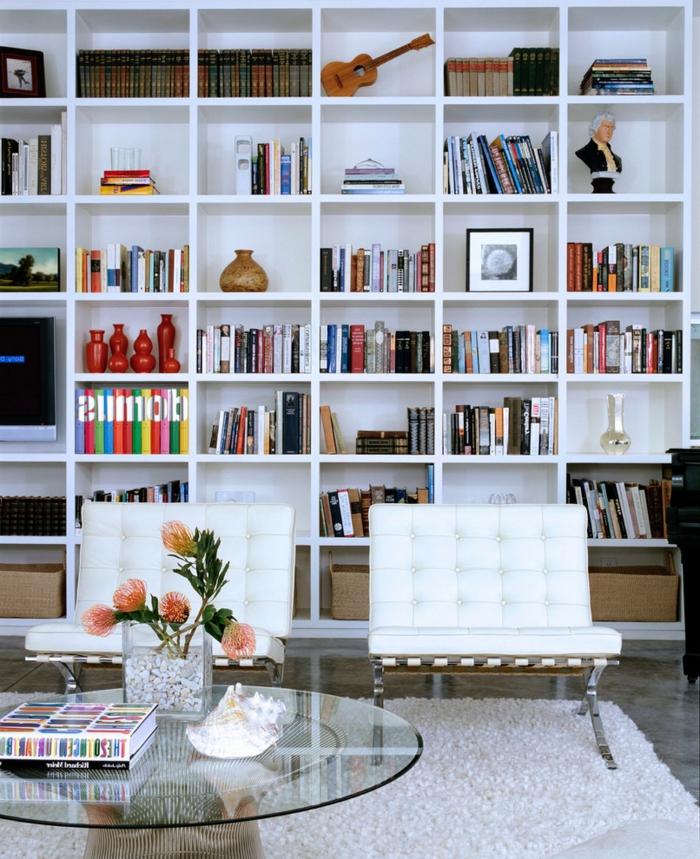 salón con librería de madera blanca, sillones tapizados en capitoné, mesa redonda de vidrio con flores, librerias, decoraciones con jarrones, estatuillas