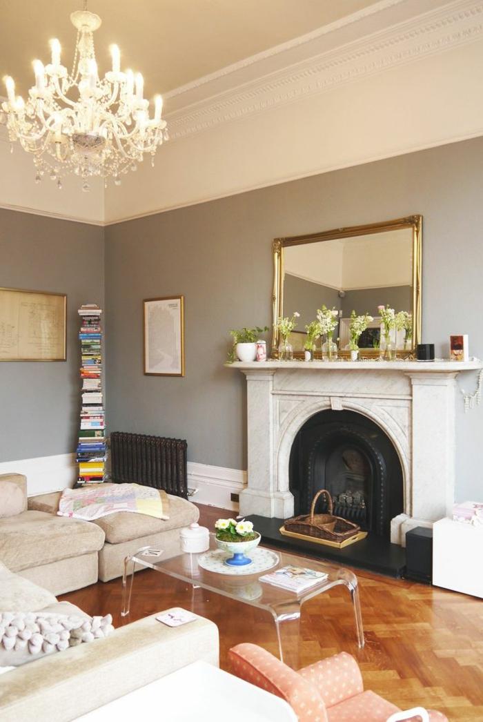 colores para salones, decoración clásica, paredes en gris y blanco, suelo con parquet, chimenea, espejo grande con marco dorado, sofá y mesa de plástico transparente