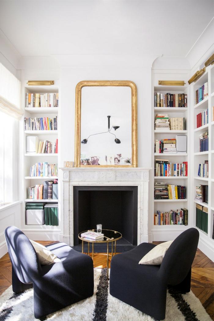 salón con librerías empotradas, chimenea con espejo grande en marco color dorado, estanterias de pared, suelo de parquet, sillones negros