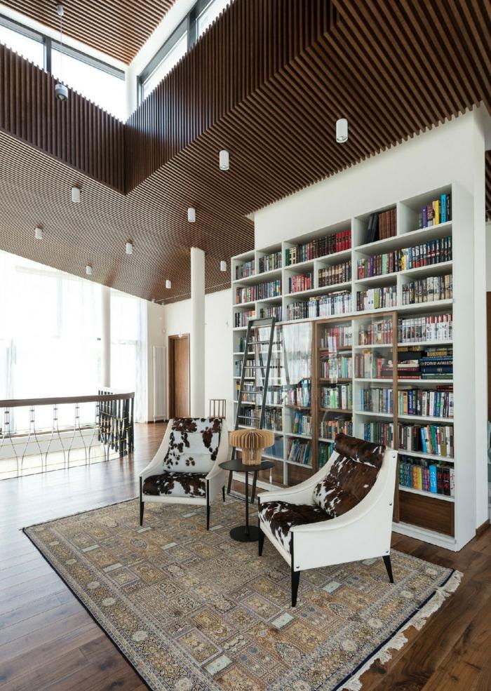 decoración en marrón y blanco, salón con sillones tapizados piel de vaca, librerías, estantería alta de madera con puertas de vidrio y escalera, suelo con tarima y alfombra