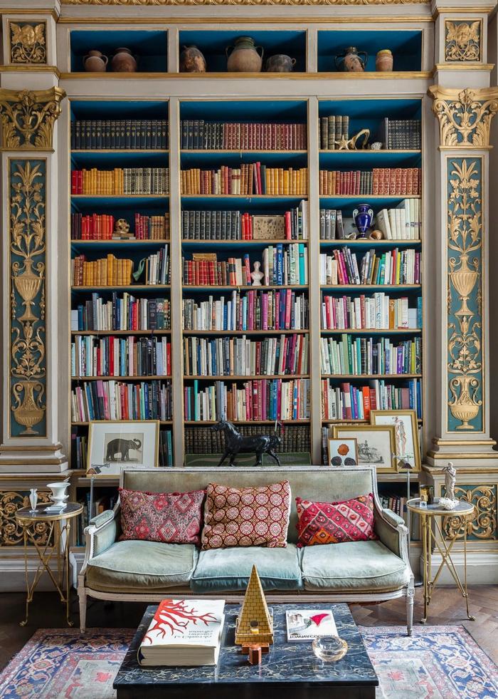 estanterias para libros, salón vintage con librería empotrada, decoración de pared con figuras en dorado, jarrones de barro, mesa de mármol, sofá con cojines, alfombra con aspecto antiguo