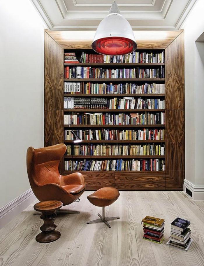 librerias, rincón de lectura con sillón tapizado de piel y taburete, librería empotrada con marco grande de madera, suelo con tarima, lámpara colgante roja de metal y vidrio