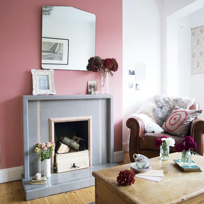 salon pequeño, paredes en rosado y blanco, combinacion de colores, chimenea con baldosas, mesa de madera vintage, espejo grande