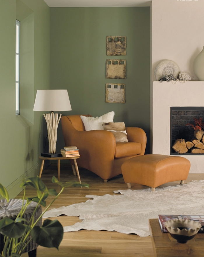 estilo rústico decoración, pintura para paredes, combinación de verde seco y blanco, sillón de piel, chimenea y alfombra piel de vaca