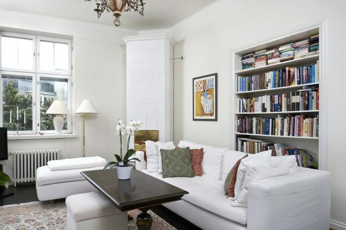 salón decorado en blanco, librería empotrada, mesa de madera con orquidea blanca, suelo laminado con alfombra, ventana pequeña, lámpara de araña, librerías