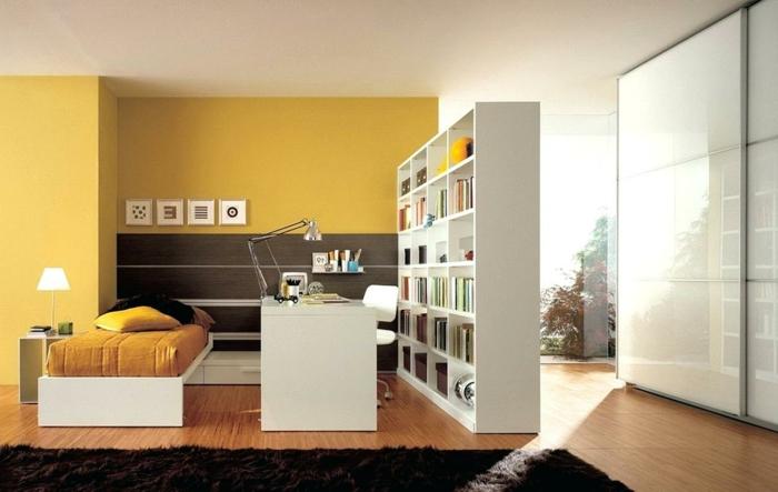 separar ambientes, grande salón con paredes en color mostaza, muebles modernos de madera, separador de ambientes en forma de biblioteca