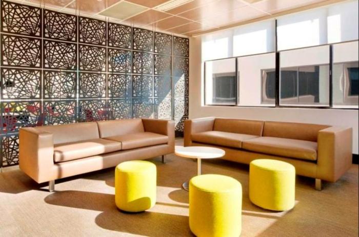 separar ambientes, grande salón con taburetes pequeños en amarillo, dos sofás en color ocre tapizado de piel