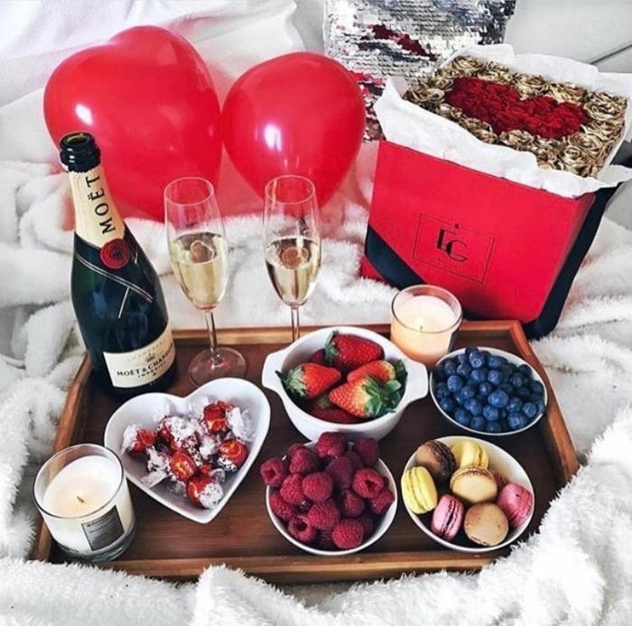 sorpresa riquísima en la cara, frutas y dulces con una botellas de champán, rosas rojas y globos, como sorprender a mi novia en San Valentín